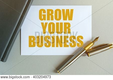 Business And Finance Concept. On The Table Are A Notebook, A Pen And A Business Card With The Inscri