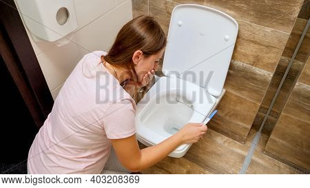 Young Woman In Pajamas Feeling Sick Vomitting In Toilet After Doing Pregnancy Test. Intoxication And