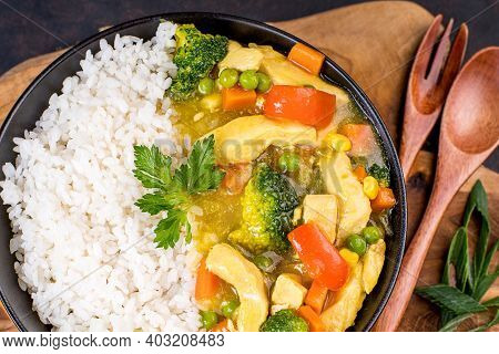 White Rice With Chicken And Vegetables And Curry Sauce. Indian Dish Rice With Vegetables And Chicken