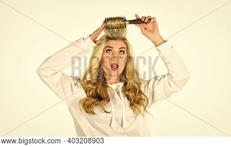 Look Your Best. Healthy Long Blond Hair. Beautiful Woman Curling Long Hair Using Curling Hairbrush.