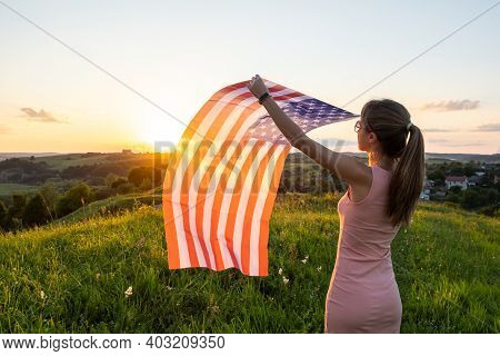 Back View Of Happy Woman With Usa National Flag Standing Outdoors At Sunset. Positive Female Celebra