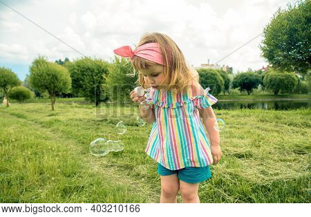 Little Beautiful Baby Girl Blowing Soap Bubbles In The City Park Ureki. Ecology And Nature Outdoors.