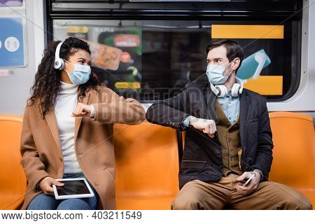 Multicultural Couple In Medical Masks Bumping Elbows And Holding Gadgets In Subway