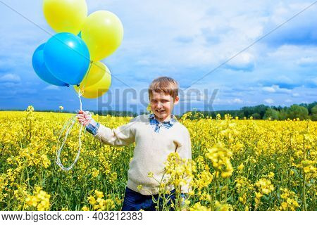Happy Boy Outdoors Helium Balloons. Run Along The Yellow Field. Rapeseed Bloom, Freedom Concept.play