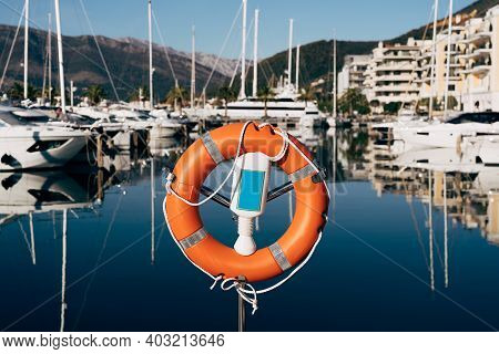 A Close-up Of A Lifebuoy On A Stand On The Dock Overlooking The Mountains And Yachts On The Water. M