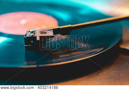 Cinemagraph Loop Vinyl Record Player Turntable With Its Stylus Running Along Music Plate. Neon Light