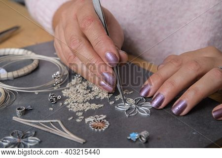 Woman - Jeweler Making Jewellery In Her Small Workshop. Repair Of Silver Jewelry. Handmade