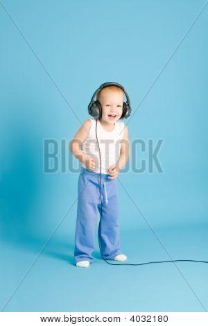 Joyful Boy Listening Music At Cord Headphones