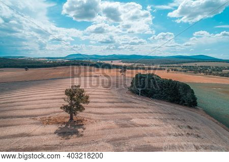 Pastoral Aerial View Of Australian Countryside With Fields And Mountains