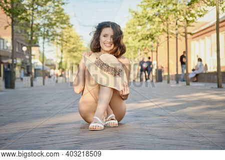Bare Young Woman In Hat Sitting At City On Cobblestone
