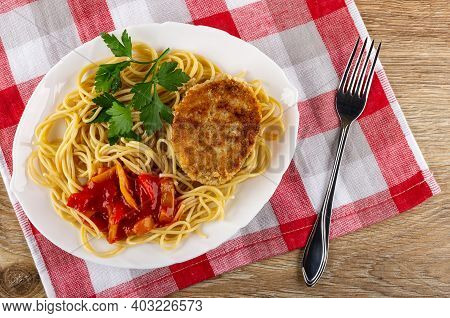 Fried Meat Cutlet With Spaghetti, Lecho, Parsley In White Glass Dish, Fork On Checkered Napkin On Wo