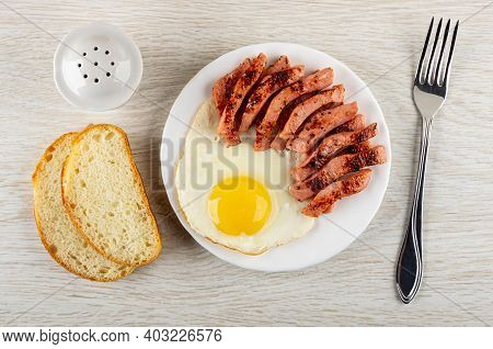 Salt Shaker, Slices Of Bread, Pieces Of Fried Sausage, Fried Egg In White Glass Plate, Fork On Woode
