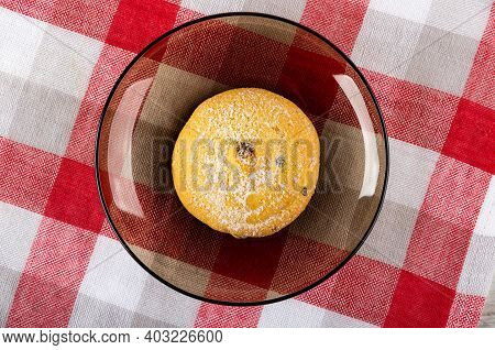 One Cookie With Raisin In Sugar Powder On Transparent Brown Saucer On Checkered Napkin. Top View
