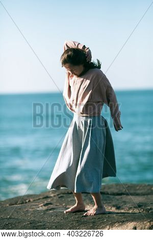 Woman is engaged in choreography on the ocean coast.