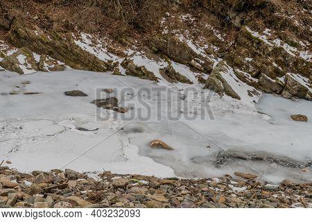 Winter Scene Of Water In River With Rocky Shoreline Frozen.