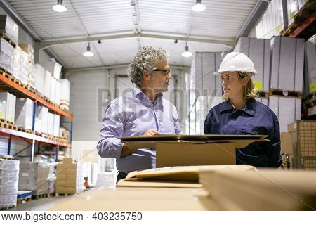 Male Safety Inspector And Female Engineer Talking In Warehouse During Inspection. Front View. Labor