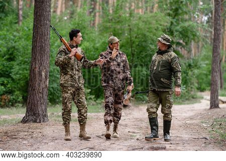 Father And Sons Hunters In Camouflage Talking.