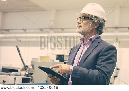 Serious Supervisor In White Helmet Holding Tablet And Looking On Manufacturing Process. Portrait Of
