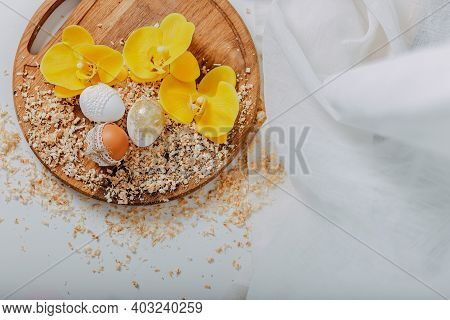 Three Easter Eggs With Yellow Orchid Flowers On Wooden Background With Sawdust Around. Easter Eggs W