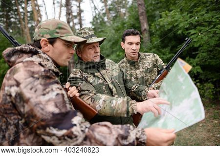Hunters Watching Map Route Planning In Forest.
