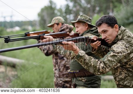 Hunters In Forest Aiming With Rifles Carefully.