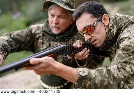 Young Man In Protective Glasses Tries To Shoot.