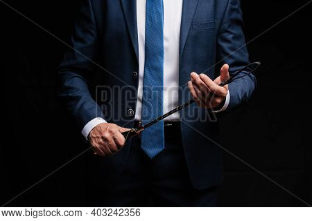 Male Dominant Businessman In A Suit Holding A Leather Whip Flogger For Domination