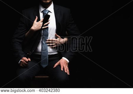 Female Arms Embrace A Male Dominant In A Suit With A Leather Whip Flogger. The Concept Of Bdsm Sex