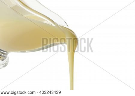 Condensed Milk Is Pouring From The Gravy Boat, Isolated On White Background