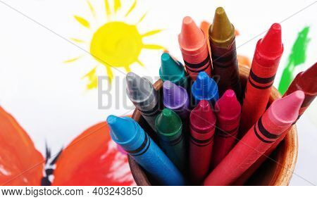 Multicolored Pastel Crayons On The Background Of Children's Drawing