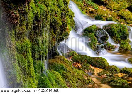 Ecology And Nature. The Source Of Clean Drinking Spring Water Among Stone Rocks And Moist Fresh Gree