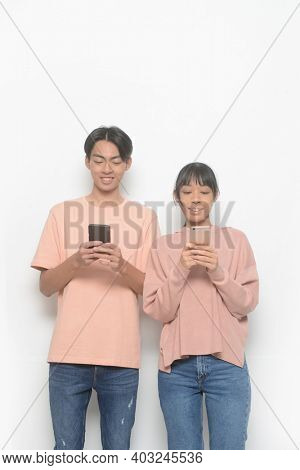 young couple. Man and woman in love in casual clothes, jeans standing using and texting on their mobile smart phones isolated on white background