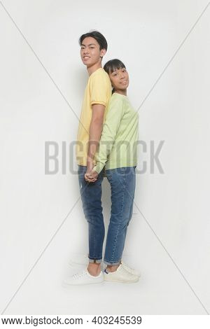 Romantic couples in love meet, hold hands,  Loving couple back to back posing on a white background.