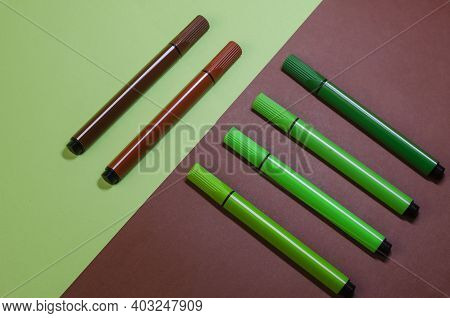 Creative Two-color Composition With Green And Brown Felt-tip Pens. Two Brown Felt-tip Pens Against F
