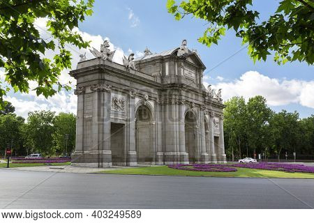 Unusual View Of The Puerta De Alcala With The Retiro Park Behind It. Famous Places Of The City Of Ma