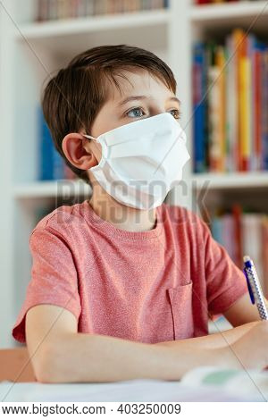 Child Self-studying During Coronavirus Outbreak. Close Up Of Child With Face Mask Looking Into Dista