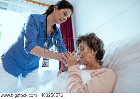 Home Caregiver Helping Elderly Woman Drink Water. Nurse Helping Sick Senior Female Patient Lying In