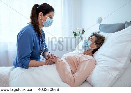 Home Caregiver Comforting Senior Female Patient Lying In Bed. Side View Of Nurse Wearing Surgical Pr