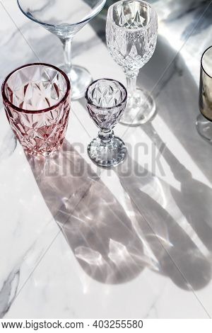 Variety Of Empty Glasses Diffrent Colors On Gray Stone Background With Hard Shadows And Sun Glare. O