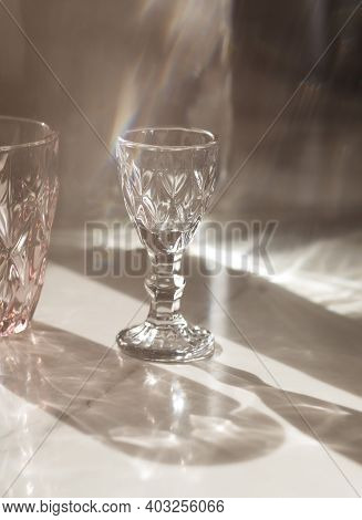 Soft Focus.variety Of Empty Glasses Diffrent Colors On Gray Stone Background With Hard Shadows And S