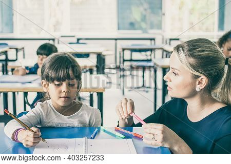 Serious Primary School Teacher Helping Girl To Cope With Her Task. Schoolgirl Drawing In Her Copyboo