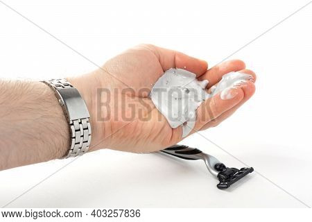 A Man's Hand With A Watch Bralet Holds A Shaving Cream In His Palm, A Shaving Machine Lies Below, A