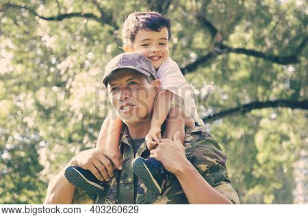 Loving Father Holding Son On Neck And Walking In City Park. Happy Caucasian Son Sitting On Neck Of D