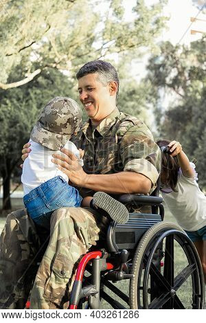 Joyful Disabled Military Dad Walking With Two Children In Park. Girl Pushing Wheelchair Handles, Boy