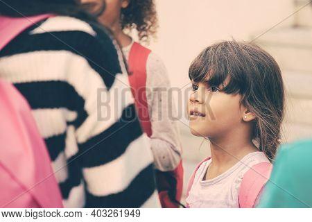 Positive Primary School Student Standing Among Elder Schoolkids. Black Haired Little Schoolgirl With
