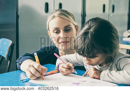 Pensive Young Female Teacher Helping Schoolgirl To Do Her Task. Little Girl Pointing At Her Open Cop