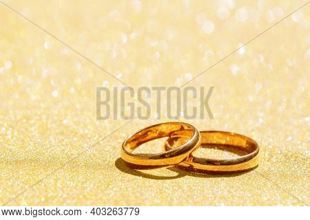 Golden Sparkling Glitter Bokeh Background With Golden Wedding Rings And Copy Space. Shallow Focus.