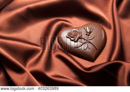 Chocolates Heart Shaped With A Pattern Of Flowers On Brown Silk. Valentine's Day Concept.
