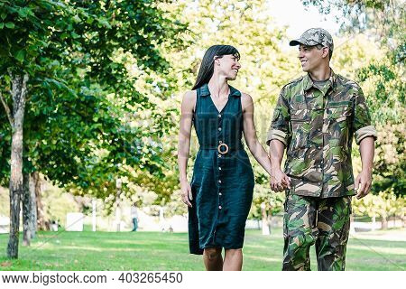 Happy Caucasian Couple Holding Hands And Walking Together On Lawn In Park. Man Wearing Military Unif