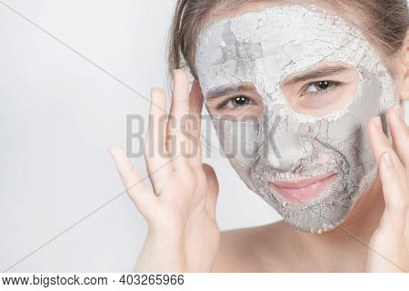 Beauty Procedures Skin Care Concept. Young Woman Applying Facial Gray Mud Clay Mask To Her Face